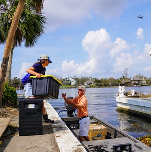 Colleen Udell and Chris Doran of Cajun Navy Relief load food donated by World Central Kitchen to deliver to the cut off island of Barataria, Louisiana, following the passage of Hurricane Ida.
