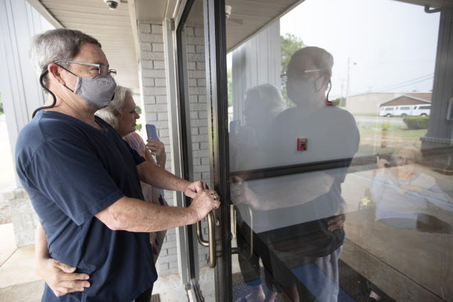Southern Pines nursing home resident Shirley Campbell visits with her daughter, Margie Price, and son-in-law, Ken, through a glass door in Warner Robins, Ga., on June 26, 2020.