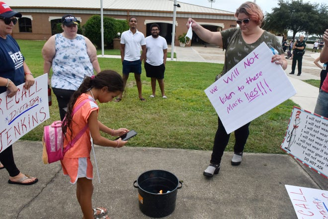 The mask mandate in public schools issue drew peaceful protest before the Brevard County School Board meeting in Viera, Fla., on September 9. One group burned masks and protested the mandate, and Moms for Liberty held a prayer circle nearby. A small group in support of masks in schools were also present.