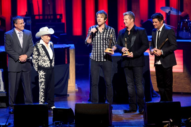 Opry General Manager Pete Fisher, left, and Little Jimmy Dickens look on as Joe Don Rooney says a few words after he and fellow Rascal Flatts members Gary LeVox and Jay DeMarcus received their induction honors as the newest members of the Grand Ole Opry on Oct. 8, 2011.
