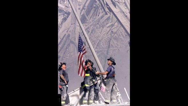 Firefighters raise a flag at Ground Zero following the attack on the World Trade Center on Sept. 11, 2001.