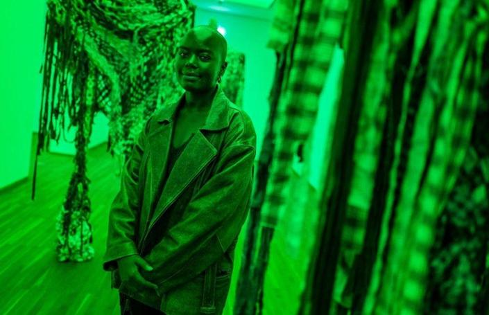 A woman stands next to an artwork in a gallery. The light is green.