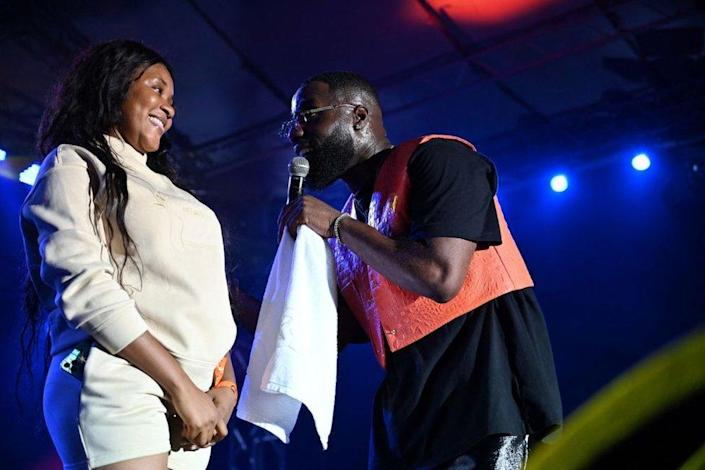 Franco-Ivorian singer Vegedream (R) performs with one of his fans on stage at the Festival of Urban Music of Anoumabo (Femua) in Abidjan on September 11, 2021.