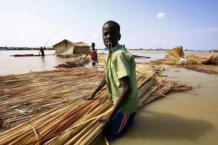 South Sudanese refugees try to repair their home in flooded waters from the White Nile at a refugee camp which was inundated after heavy rain near in al-Qanaa in southern Sudan, on 14 September.