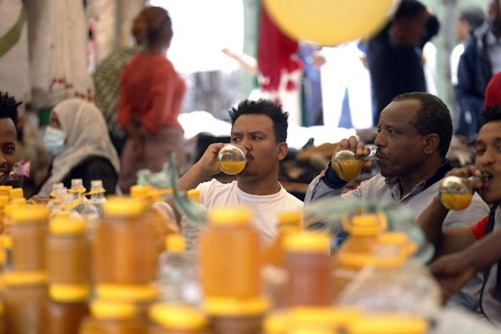 People buy Tej to drink at a market in Addis Ababa, Ethiopia.