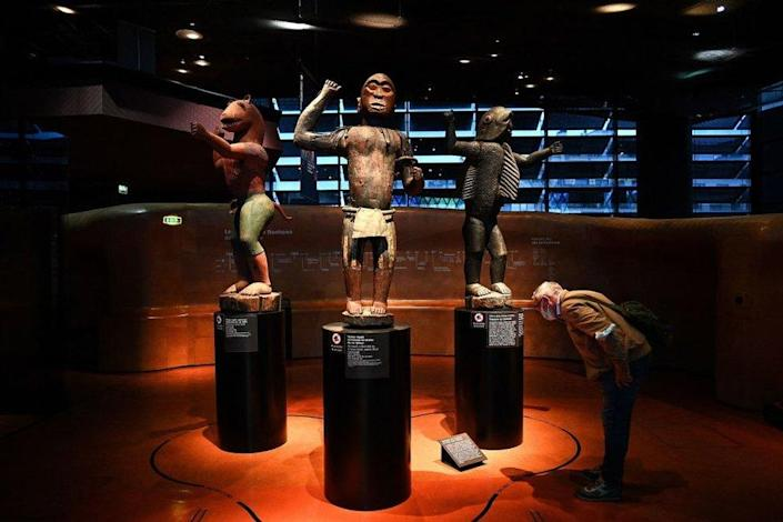 A visitor looks at statues of the Royal Treasures of the Abomey Kingdom at a museum in Paris, France, on Friday.