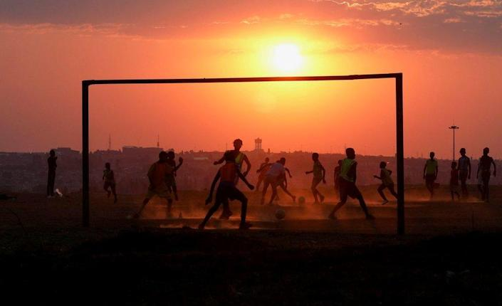 People are seen playing football through the goalposts. The sun appears large and hazy in the sky.