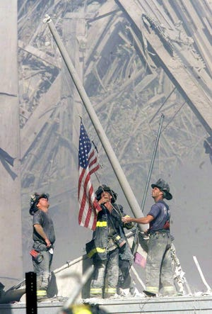 New York City firefighters raised a flag at Ground Zero in the afternoon of Sept. 11, 2001.