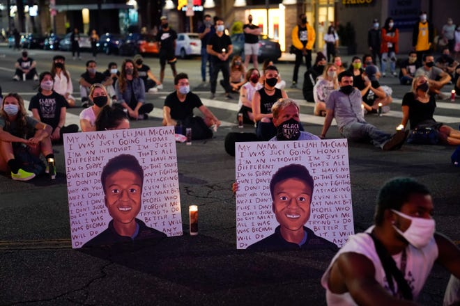 In this Aug. 24, 2020, file photo, two people hold posters showing images depicting Elijah McClain during a candlelight vigil for McClain outside the Laugh Factory in Los Angeles. An investigation into the arrest of McClain in suburban Denver criticizes how police handled the entire incident, faulting officers for their quick, aggressive treatment of the 23-year-old unarmed Black man and department overall for having a weak accountability system.