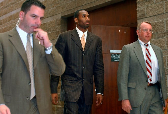 In this 2004 file photo, Kobe Bryant, center, walks out of a holding area for a lunch break from proceedings in his sexual assault case as members of his security team accompany him, in Eagle, Colo.