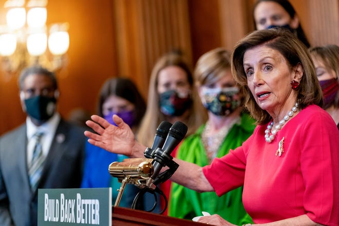 """House Speaker Nancy Pelosi, D-Calif., accompanied by other House Democrats and climate activists, pauses while speaking about their """"Build Back Better on Climate"""" plan on Capitol Hill in Washington on Sept. 28, 2021."""