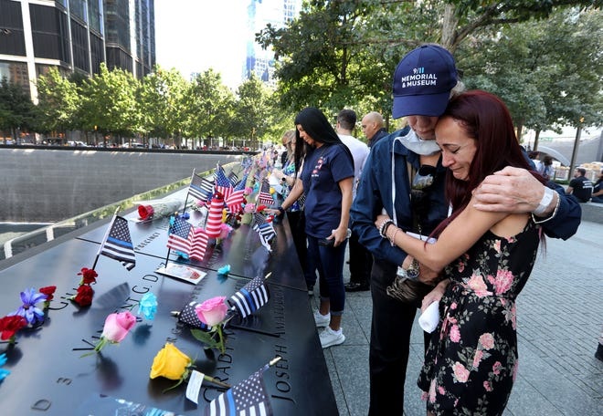 Mercedes Arias, formerly of Yonkers, N.Y., is comforted by a 9/11 Museum staff member as she cries near the name of her father, Joseph Amatuccio at the 9/11 Memorial Sept. 11, 2021. Arias was attending the ceremony marking the 20th anniversary of the Sept. 11th attacks. Her father, who worked in the World Trade Center, died in the attacks.