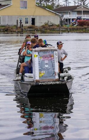 Tess Coulon, in the pink hat, rides back to her hometown island of Barataria, Louisiana, which was cut off from the mainland after the passage of Hurricane Ida. Coulon's washing machine broke after the storm and she traveled to the mainland to get a new one so she and her family could have clean clothes while they wait for the road to be repaired.