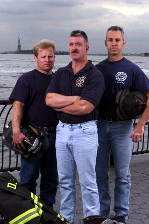 George Johnson, Dan McWilliams, and Bill Eisengrein (left to right) pose for photo with Statue of Liberty in background on August 30, 2002, one year after the photo of the three New York City firemen raising the U.S. flag at Ground Zero was taken by Thomas E. Franklin of The Record.