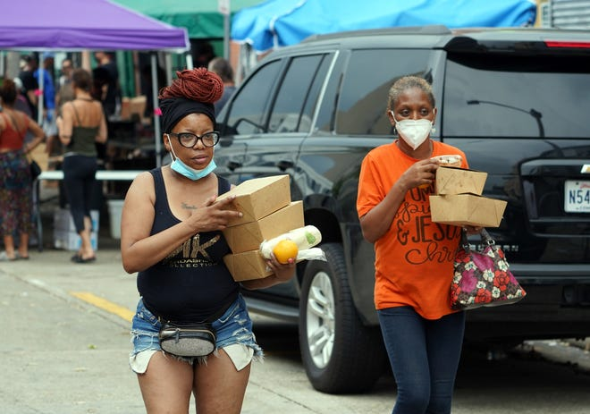 Trenise Cooper, 57, left, walks with a friend after picking up free meals at a World Central Kitchen feeding station in New Orleans on Monday, Sept. 6, 2021, following the passage of Hurricane Ida.