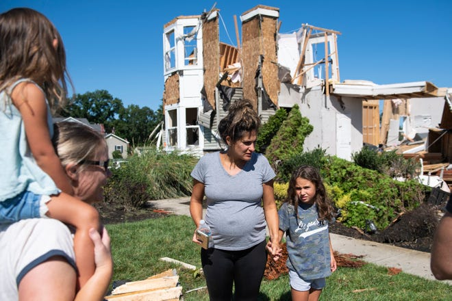 Ashley Thomas, left, with her daughter Kenley Thomas, 6, Thursday, Sept. 2, 2021 after their home was severely damaged by a tornado in Mullica Hill, N.J.
