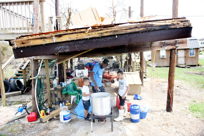 Kentrell Garner, center, uses bottled water to boil shrimp with the help of his sons, Kaviyon, left, and Mali'K, underneath what was their home Friday, Sept. 3, 2021, in Grand Caillou, Louisiana.