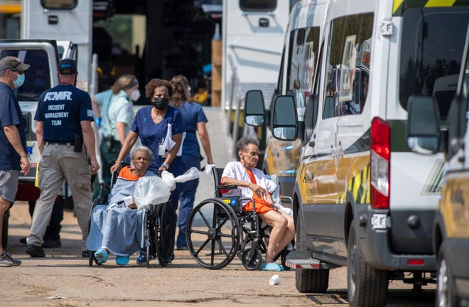 Paramedics evacuate people at a mass shelter Thursday, Sept. 2, 2021 in Independence, La. Multiple nursing home residents died after Hurricane Ida, but full details of their deaths are unknown because state health inspectors said Thursday that they were turned away from examining conditions at the facility to which they had been evacuated.