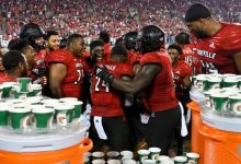 Teammates celebrate with Louisville linebacker Jaylin Alderman after he intercepted a pass and returned it for a touchdown against UCF.