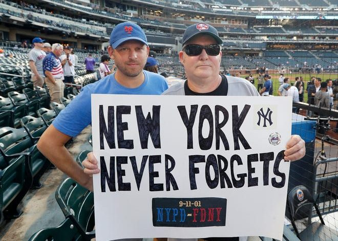 New York Yankees fan John Broder, right, and New York Mets fan Cory Schwartz hold up a poster board in reference to the 9/11 terrorist attacks prior to Saturday night's game at Citi Field.