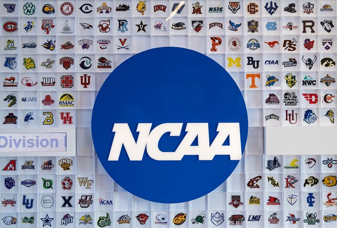 University logos cover a wall in the lobby of NCAA headquarters Thursday, Feb. 25, 2021, in Indianapolis.