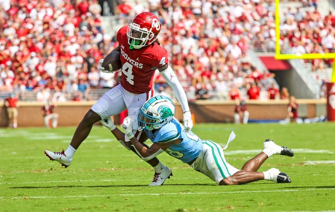 Oklahoma wide receiver Mario Williams (4) runs with the ball as Tulane defensive back Jadon Canady (28) defends during the first quarter.