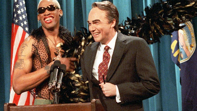 Dennis Rodman throws a feather boa around the shoulders of Norm MacDonald, playing Bob Dole, during a dress rehearsal for SNL on May 11, 1996. (Mary Ellen Matthews, AP)