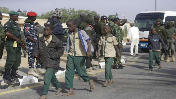 A group of schoolboys are escorted by Nigerian military and