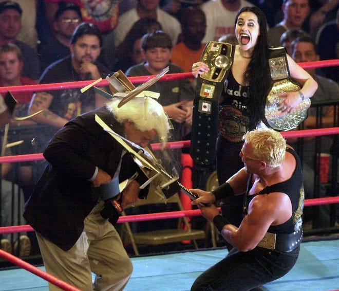 Daffney Unger looks on as Jeff Jarrett, right, smashes a guitar over the head of Ric Flair during WCW's Monday Nitro in Biloxi, Miss., on May 15, 2000.