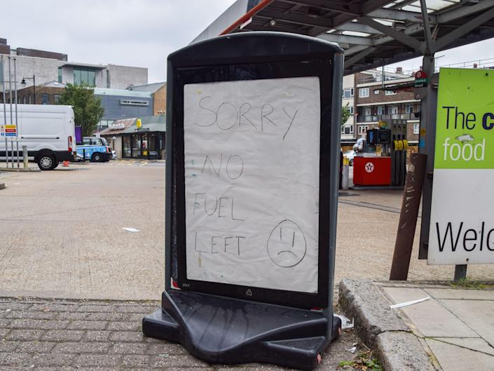 """Sign at petrol station saying """"sorry no fuel left""""."""
