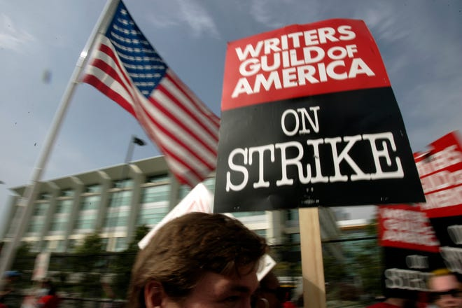 In this 2007 file photo, Writers Guild of America members strike against the Alliance of Motion Picture and Television Producers in a rally at Fox Plaza in Los Angeles' Century City district.