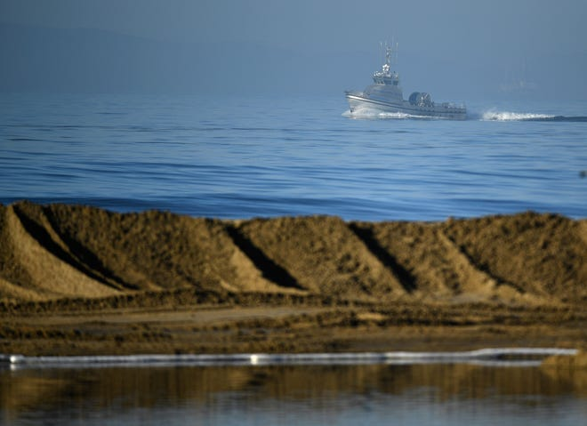 Boats helping clean up an oil spill are seen from the shore in Huntington Beach, California on October 3, 2021.