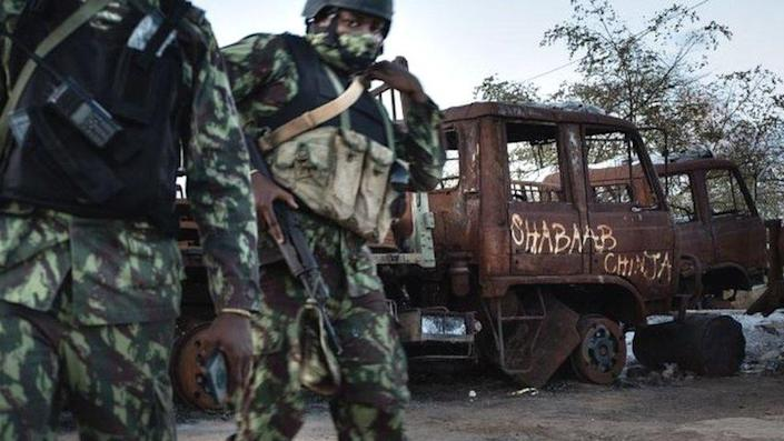 """Mozambican soldiers patrol in front of a burned truck carrying the inscription """"Shabaab Chinja"""" referring to the jihadist group in Mocímboa da Praia -22 September 2021"""