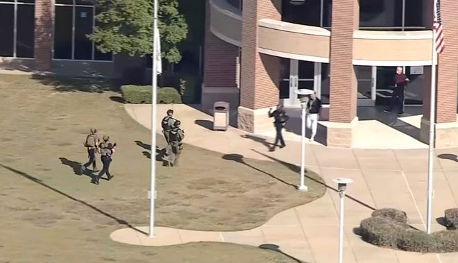 In this image from WFAA-TV video, law enforcement arrives at Timberview High School on Wednesday, Oct. 6, 2021 in Arlington, Texas. Authorities say a student opened fire inside the Dallas-area high school during a fight.