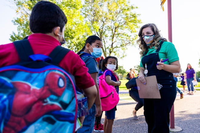 A Garden Place Elementary School teacher in Denver welcomes students for their first school day on Aug. 23. Teachers are eligible for the Public Service Loan Forgiveness program, but many have been denied forgiveness because of technical errors with their applications.