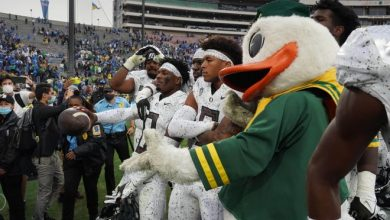 Oregon cornerback DJ James (0) poses with teammates and The Oregon Duck after the Ducks defeated UCLA.