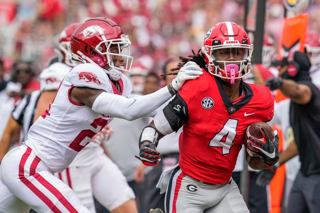 Georgia Bulldogs running back James Cook (4) gets knocked out of bounds by Arkansas Razorbacks defensive back Montaric Brown (21) during the first quarter at Sanford Stadium.