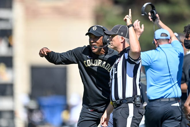 Colorado coach Karl Dorrell talks to a referee in the first quarter of a game against the USC Trojans at Folsom Field.