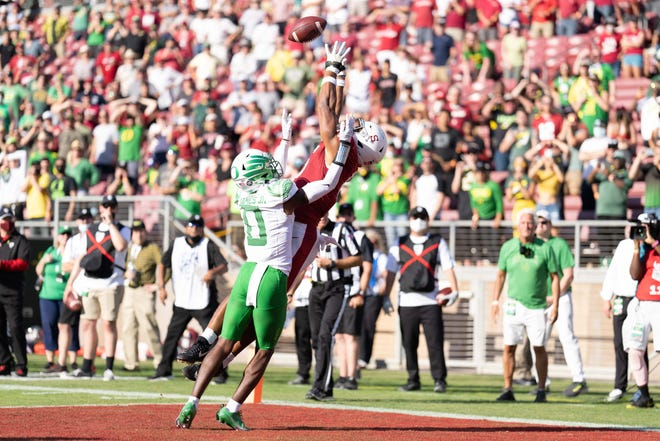 Cardinal wide receiver Elijah Higgins catches the ball for a touchdown during the fourth quarter against Ducks cornerback DJ James.