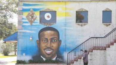 A man uses his phone to record the Ahmaud Arbery mural on the side of the Brunswick African American Cultural Center.