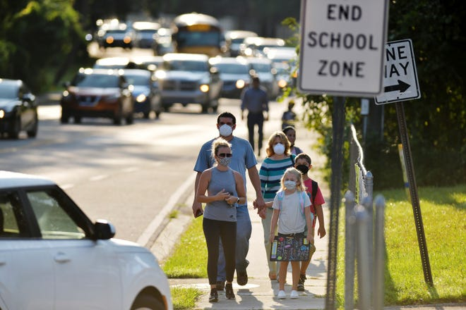 Students and parents make their way to school on Aug. 1, 2021, in Jacksonville, Fla.